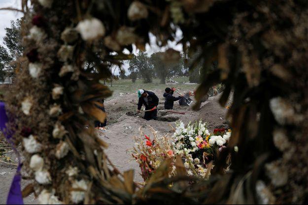 Des employés d'un cimetière creusent de nouvelles tombes dans une zone désignée pour les personnes décédées du coronavirus au cimetière de San Lorenzo Tezonco à Mexico, Mexique.