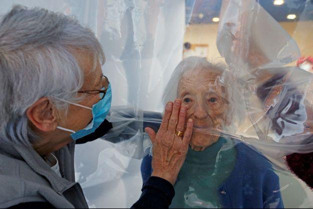 Une fille est autorisée à toucher sa mère, résidente dans une maison de retraite, à travers une bulle de protection en plastique contre le covid-19, à Jeumont, dans le Nord.