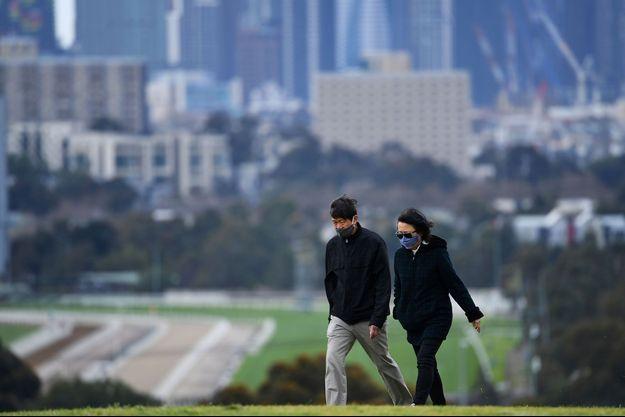 Deux personnes masquées marchent à Melbourne.