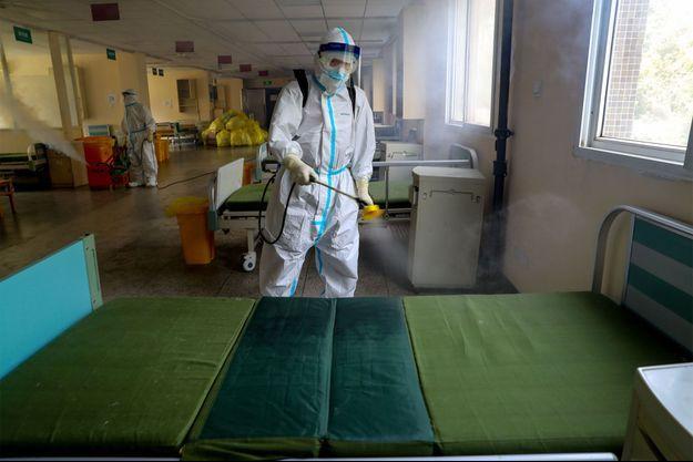 Des employés de désinfection nettoient l'hôpital numéro 7 de Wuhan, en Chine.