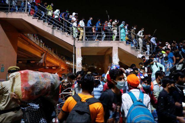 A New Dehli, les bus sont pris d'assaut pour partir avant le début du confinement.