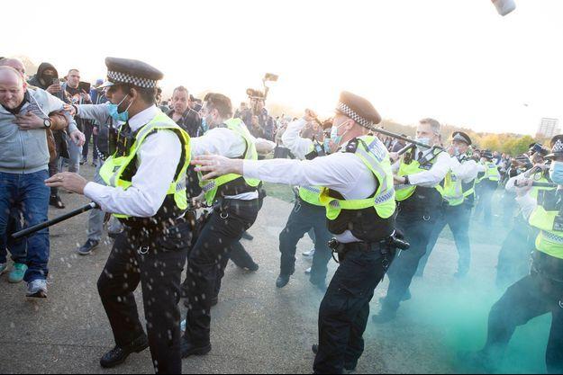 Heurts entre policiers et manifestants durant un rassemblement de grande ampleur samedi à Londres contre les dernières restrictions sanitaires imposées en Angleterre.