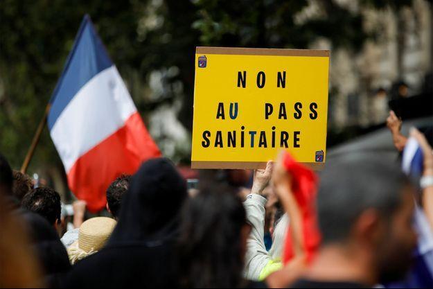 Une affiche tenue lors d'une manifestation contre le pass sanitaire à Paris.