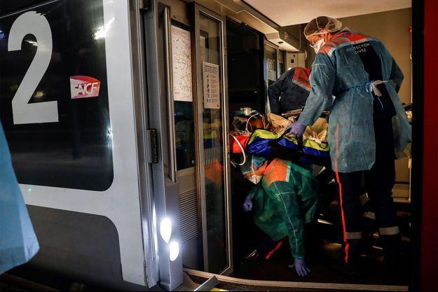 Des soignants transfèrent des patients infectés par le COVID-19 à bord d'un TGV à la gare d'Austerlitz vers la Bretagne.