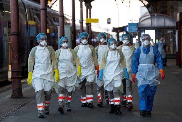 Des soignants attendent qu'un patient malade du coronavirus embarque dans un TGV médicalisé, à Strasbourg.