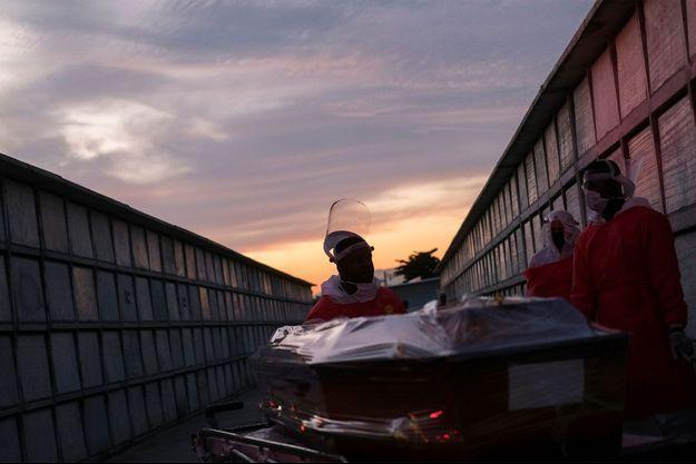 Des fossoyeurs préparent le cercueil d'un homme soupçonné d'être décédé du coronavirus, au cimetière public Duque de Caxias, près de Rio de Janeiro, au Brésil.