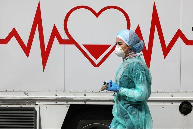 Une médecin jordanienne parcourt une clinique mobile qui fonctionne dans le cadre d'une initiative lancée dans le but de fournir aux Jordaniens des services médicaux sur le terrain, face à la propagation de la maladie à coronavirus, à Amman, en Jordanie.