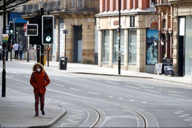 Un homme marche dans une rue de Manchester.