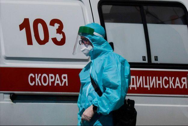 Un soignant marche près d'une ambulance, à Moscou.