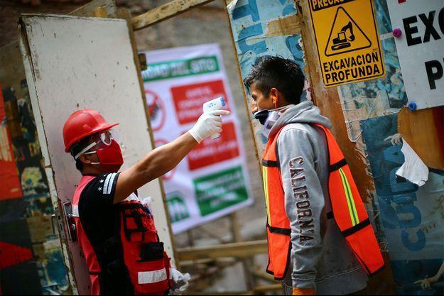 Alors que le Mexique débutait lundi sa réouverture progressive, un ouvrier se fait prendre sa température avant de pouvoir accéder au chantier.