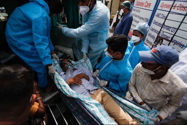 Un malade du covid-19 transporté à l'hôpital, à Bombay, le 23 avril.