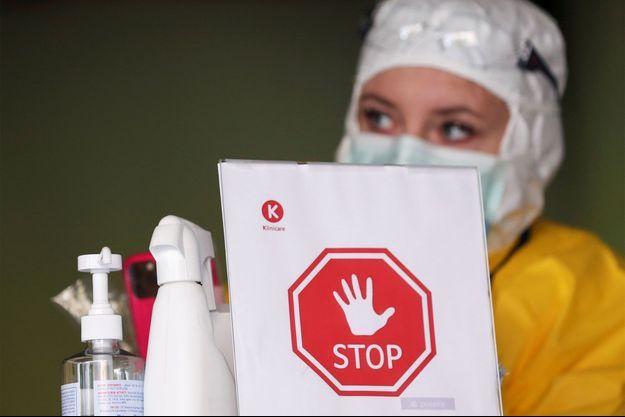Un employé du centre médical Klinicaire attend à l'entrée d'une zone de contrôle destinée à examiner les patients souffrant de symptômes de coronavirus à Bruxelles.