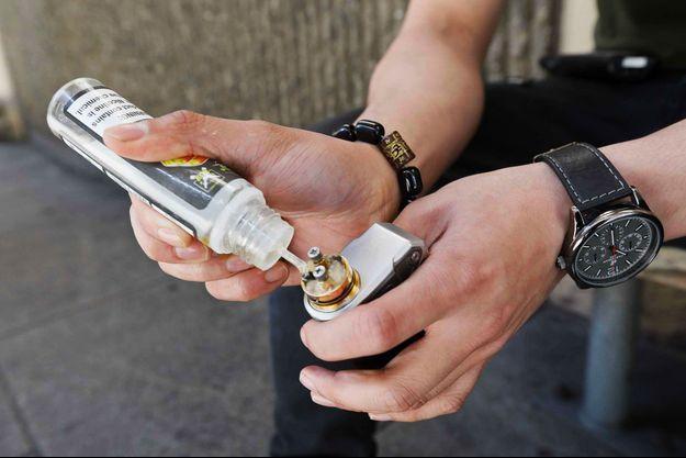 Un utilisateur de cigarette électronique recharge son appareil à San Francisco, en juin 2019. (photo d'illustration)