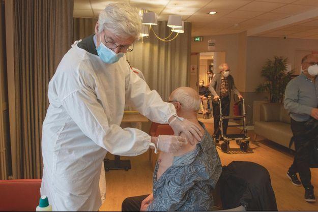 Le docteur Marc Henry administre le vaccin Pfizer-BioNTech à son confrère, Bernard Francoz, à l'Ehpad des Amandiers, dans l'Est parisien, le 7 janvier.
