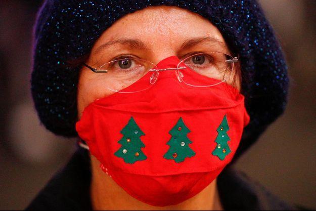 Une femme dans les rues de Rome avec un masque aux couleurs de Noël.