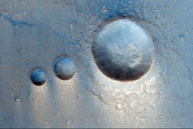 Les trois cratères martiens dans la région de Lunae Planum.