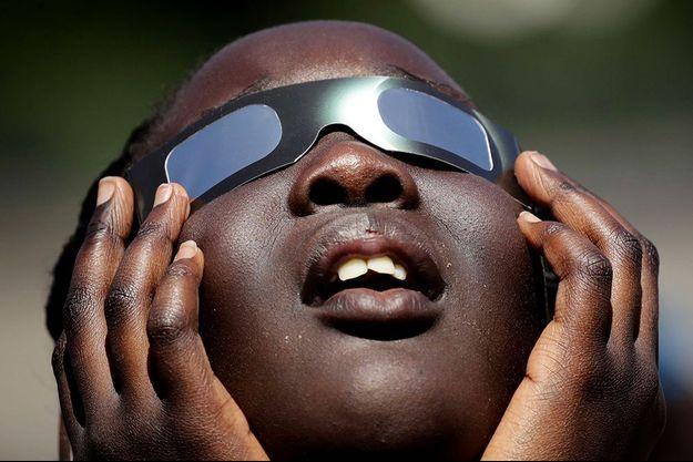 Un enfant s'entraîne à utiliser ses lunettes pour observer l'éclipse.