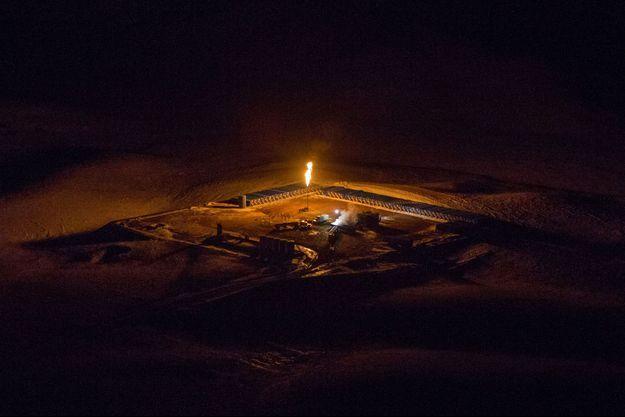 Vue d'un puit de gaz naturel qui procède à un torchage en pleine nuit, dans l'Etat du Dakota du Nord.
