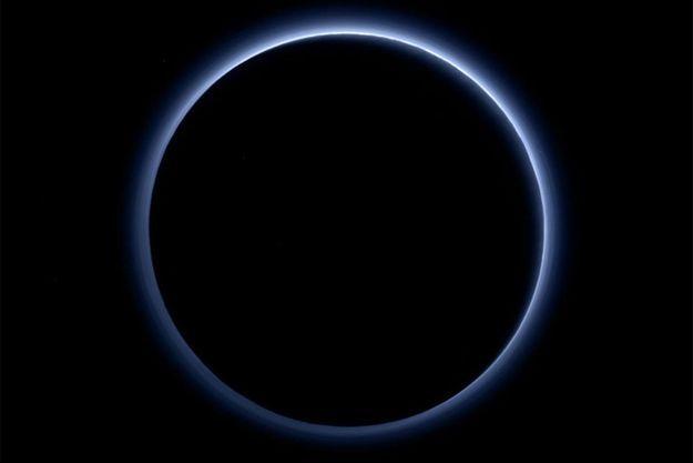 Les particules rouges ou grises qui forment la brume entourant Pluton sont suffisamment petites pour diffuser la lumière bleue du soleil, de la même manière que dans le ciel terrestr