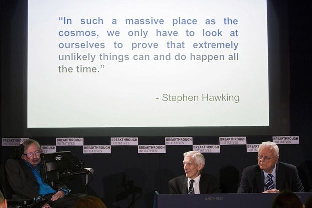 """Le lundi 20 juillet lors de la présentation du projet Breakthrough Listen à la Royal Society à Londres. De g. à d.: Stephen Hawking, le cosmologue Martin Rees et l'astronome, Francis Drake. Sur l'écran, une phrase de Stephen Hawking: """"Dans un lieu si vaste que le cosmos, il suffit de nous regarder nous-mêmes pour comprendre que des évènements très improbables peuvent survenir et surviennent tout le temps."""""""
