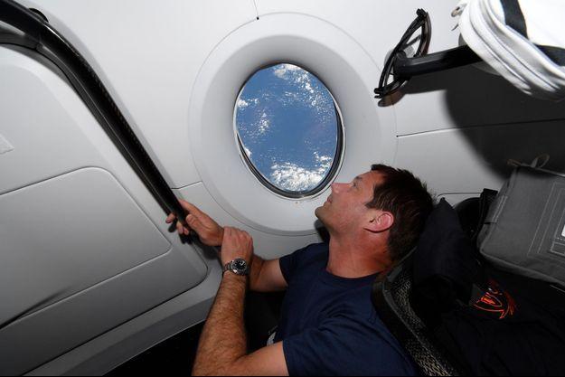 Thomas Pesquet regarde la Terre depuis une fenêtre de l'ISS.
