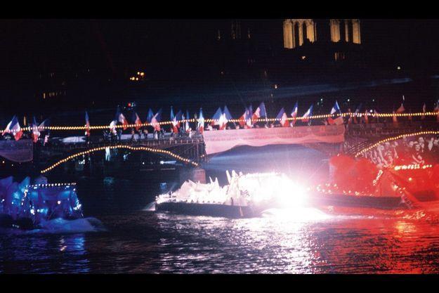 Sur la Seine, nos trois couleurs illuminent les barges de la victoire.