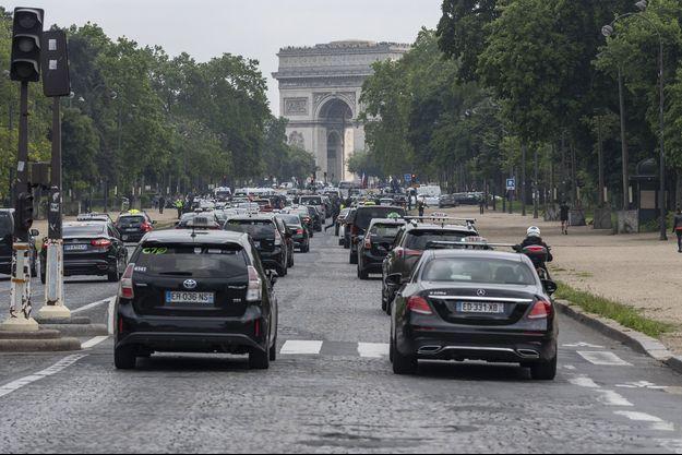 Des voitures arrivent place de l'Etoile à Paris.