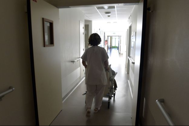 Une soignante transporte une personne âgée dans un EHPAD. Image d'illustration.