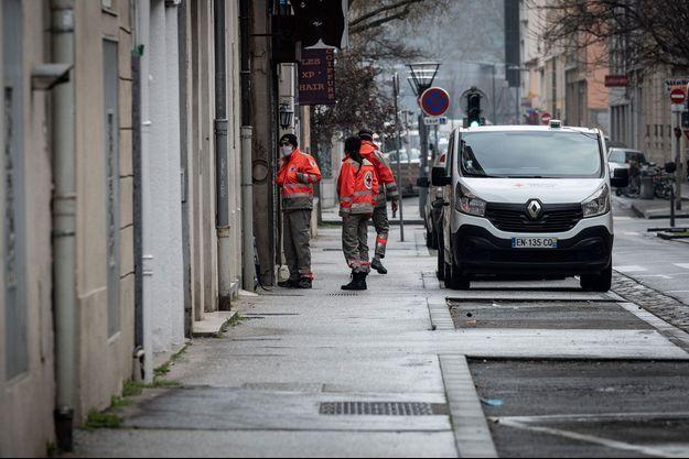 Des membres de la Croix-Rouge font du porte-à-porte pour vérifier qu'aucun habitant n'est resté chez lui, dans le quartier de la Vaise, à Lyon, dimanche.