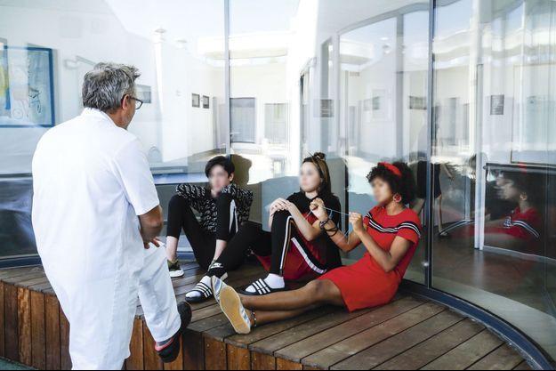 Dans la cour intérieure des services pour adolescents de l'hôpital Charles-Perrens de Bordeaux, le 17 juin 2019. En fin d'après-midi, Vincent, l'infirmier, discute avec Florian, 14 ans, Océane, 15 ans, et Lucie, 14 ans, qui fait un scoubidou.