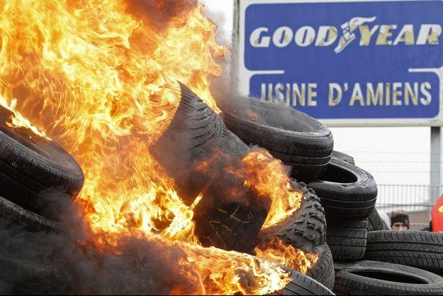 Des salariés de Goodyear brûlent des pneus devant l'usine, à Amiens, en 2013.