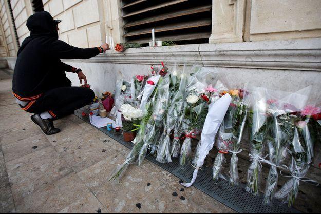 Un homme dépose lundi une bougie en mémoire des deux jeunes femmes tuées à la gare Saint-Charles, à Marseille, dimanche.