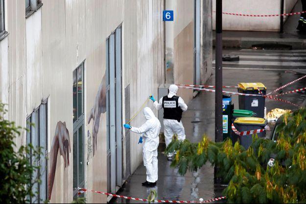 Les enquêteurs près des lieux de l'attaque à l'arme blanche, vendredi, à Paris.