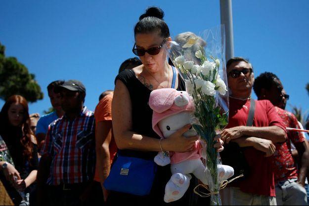 Une femme apporte une peluche sur les lieux de la tragédie, Promenade des Anglais, à Nice