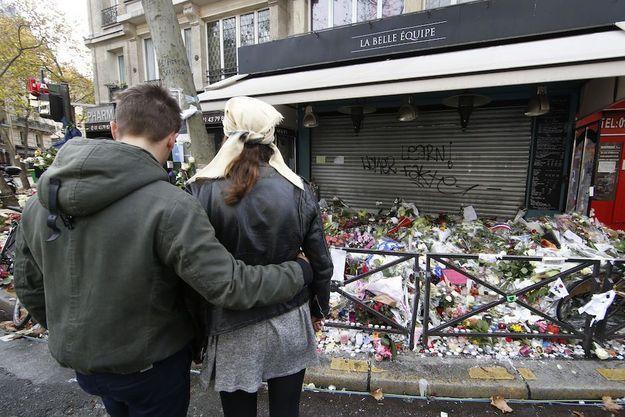 """Un couple se recueille devant le café """"La Belle équipe"""" mardi 17 novembre 2015."""