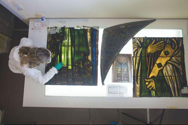 Claudine Loisel, responsable du pôle vitrail au LRMH, ausculte la robe du roi David (XIXe siècle). Au centre, un plan de Notre-Dame et au milieu, sous une pièce presque noire, la photo de référence du vitrail « David et Abraham », en 2014.