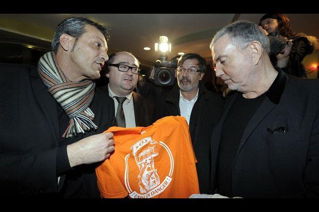 """Le 16 décembre 2011 à Florange, lors d'un concert de soutien aux ouvriers d'Arcelor Mittal, Bernard Lavilliers reçoit un tee-shirt """"SOS Usines en danger""""."""