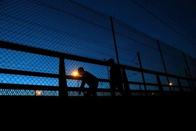 Deux migrants tentent d'accéder au tunnel sous la Manche.