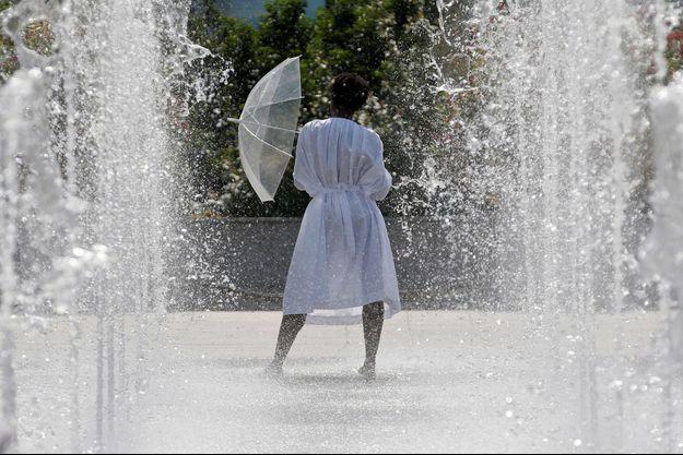 Une femme se rafraîchit dans une fontaine, à Paris.