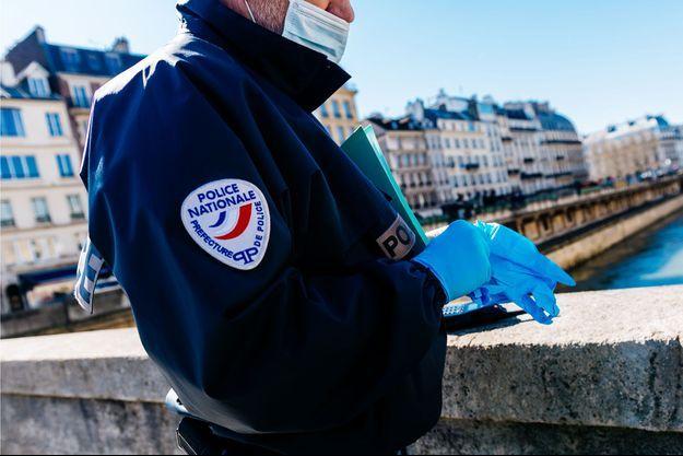 Image d'illustration. Un policier avec des gants et un masque lors d'un contrôle à Paris, le 23 mars.