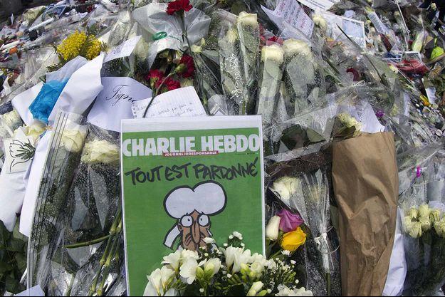 """Des fleurs et un exemplaire de """"Charlie Hebdo"""" devant les bureau du journal satirique, en 2015."""