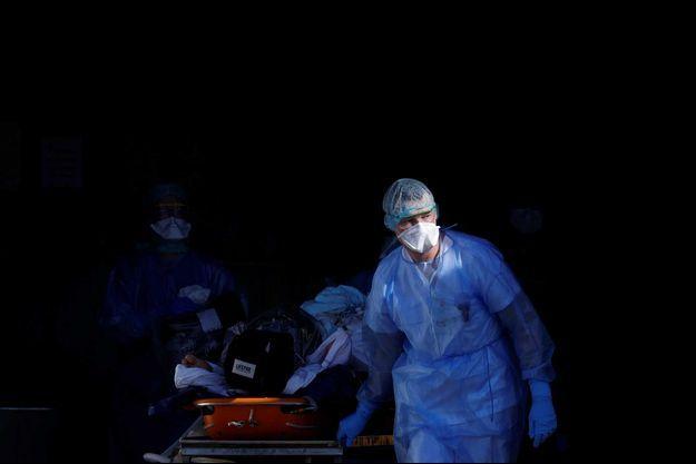 Un soignant transporte un malade du coronavirus qui s'apprête à être transféré en Allemagne, le 24 mars, à Strasbourg.