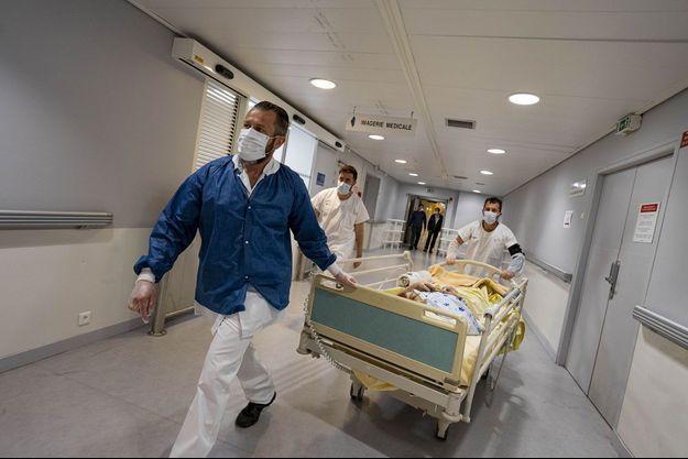 Olivier tire un brancard, aidé par Bruno, à l'hôpital Henri-Mondor de Créteil, le 7 mai.