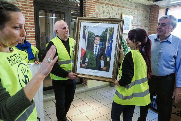 Ici des militants du mouvement ANV-COP21 enlève le portrait de Macron à Cabestany, le 27 février.