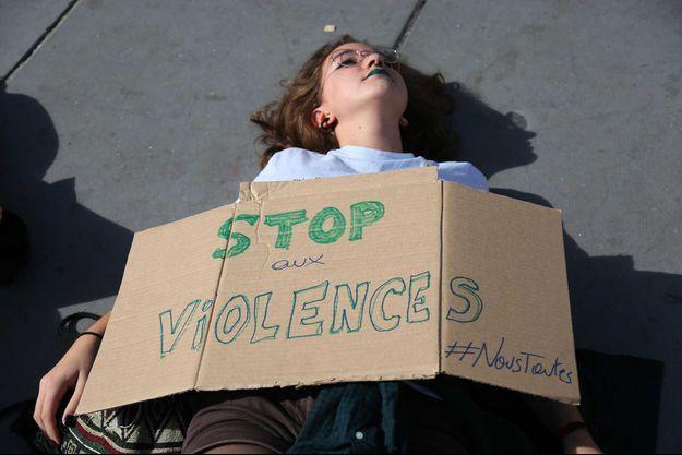 """Place de la République à Paris, une femme manifeste avec une pancarte """"Stop aux Violences""""."""