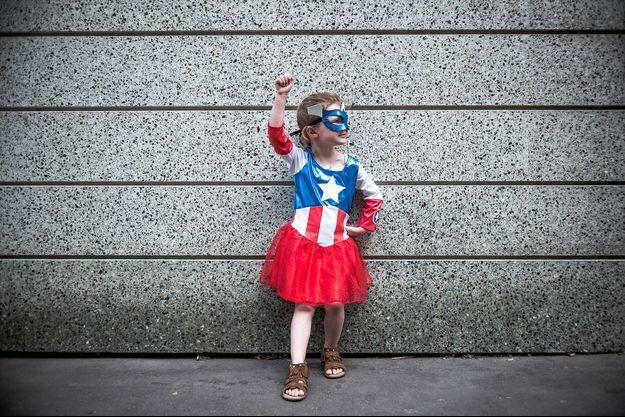Une petite fille porte un costume de super-héroïne. Image d'illustration.