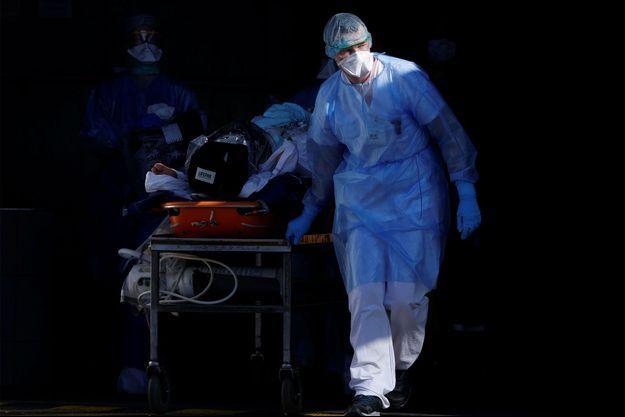 Un patient infecté par le coronavirus est transporté sur une civière par une équipe de secours française avant d'être transféré par un hélicoptère de la sécurité civile du CHU de Strasbourg à Pforzheim en Allemagne.