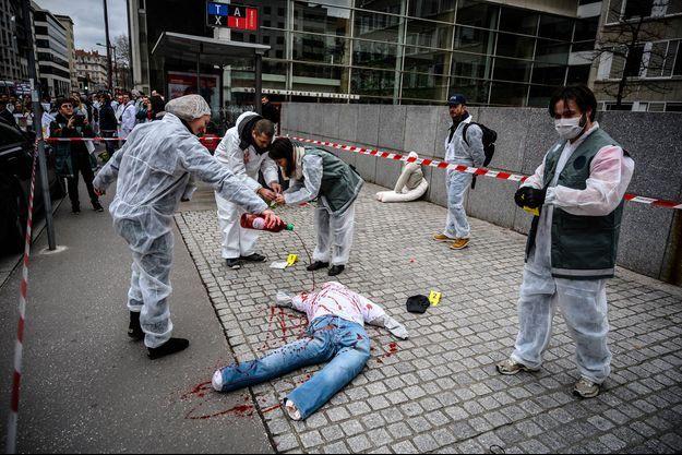 """Les manifestants avaient placé devant le Tribunal de grande instance deux faux cadavres, du faux sang et à terre des pancartes choc: """"Attentat du Bataclan, j'y étais"""", """"Attentat de Nice, j'y étais"""", """"Charlie Hebdo, j'y étais""""."""