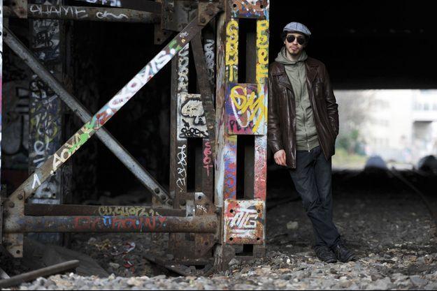 Farid Benyettou sous un pont de l'ancienne voie de chemin de fer du parc des Buttes-Chaumont, à Paris, le 18 décembre 2016. Pour la photo, l'ex-prédicateur refuse d'enlever ses lunettes noires.