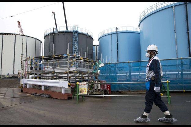 23 février 2017, un employé passe devant des réservoirs de stockage d'eau contaminée à la centrale nucléaire de Fukushima.